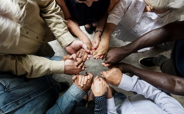 Group of diverse hands holding each other in supportive teamwork