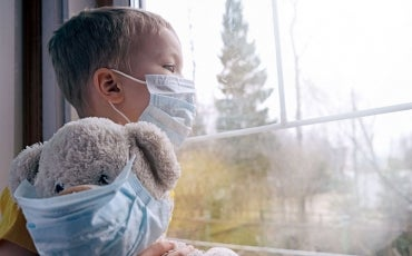 Sad child in quarantine with mask and masked teddy bear