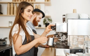 Female and male baristas in cafe