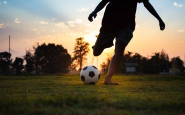 A young person plays soccer on an open field alone, with the sun setting behind them.