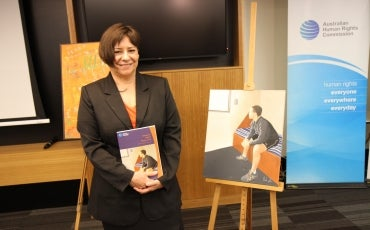 Image of Megan Mitchell at the launch of the Children's Rights Report. To Megan's right is a painting by a young person in youth justice detention. That painting is also the cover of the Children's Rights Report.