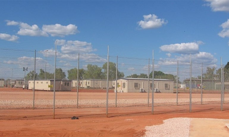 Immigration detention centre in dusty field