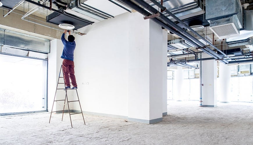Worker on ladder fitting ceiling appliance