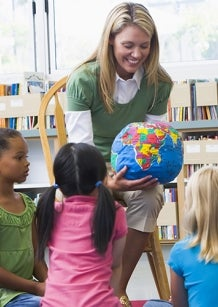 teacher showing globe to class