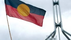 Aboriginal flag with Parliament House Canberra